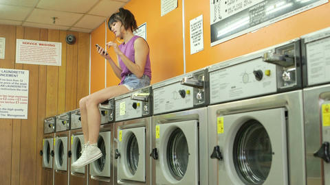 Low Angle MLS A Young Woman sits waitng in a Launderette Footage