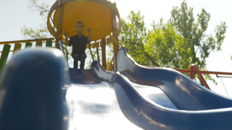 Happy joyful kid sliding down a blue slide on a playground in a park Footage