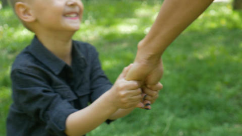Smiling kid pulling his mother hand asking to play with him in the park Footage