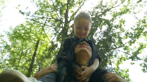 Kid standing on mother shoulders while the two are spinning around in the forest Footage