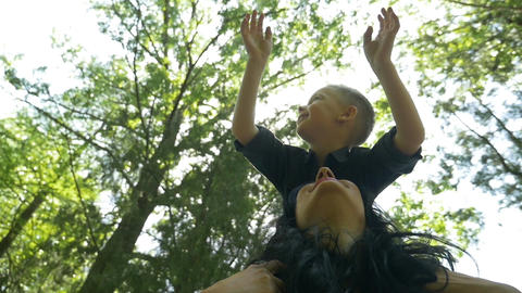 Child smiling while standing on mother shoulders enjoying his recreational time  Footage