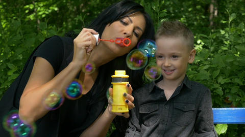 Mother entertaining and teaching her boy making iridescent soap bubbles on a ben Footage