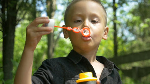 Closeup of happy cute boy blowing colored soap bubbles in sunny park Footage