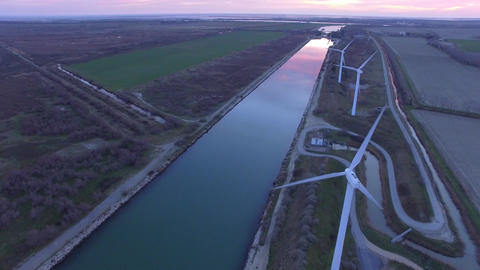 Wind Farm along a canal in Camargue, filmed by drone at sunset, France Footage