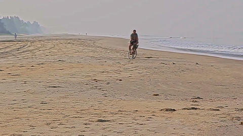 Young Man Rides Bike along Empty Sand Ocean Beach Footage
