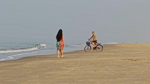 Beautiful Woman Walks on Beach with Young Man Riding Bike Footage
