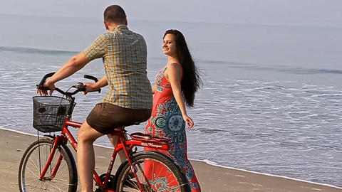 Woman Walks along Beach and Smiles to Man on Bicycle Footage