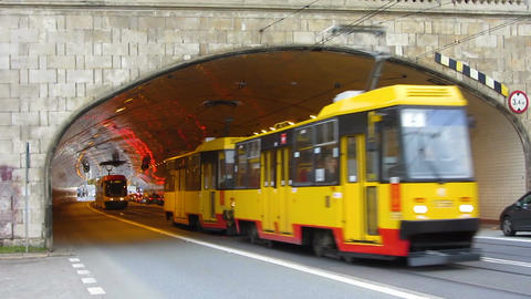 Trams and other vehicles hurrying, moving out from under bridge on wide motorway Footage