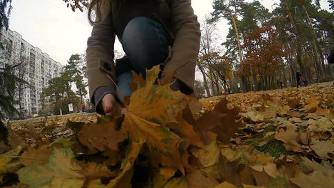 Lonely woman walking through autumn park, throwing up fallen golden leaves Footage