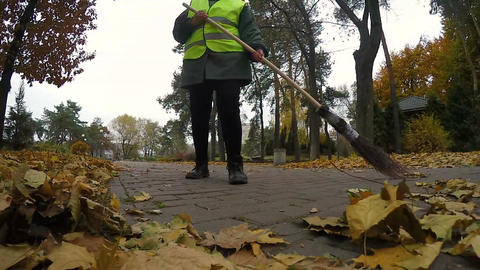 Woman janitor cleaning park from leaves in autumn, most hard and low-paid job Footage