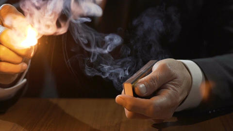 Rich man in expensive suit lighting up Cuban cigar with a match, smoking male Footage