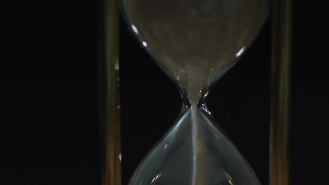 White sand running fast through hourglass measuring time, life value, close-up Footage