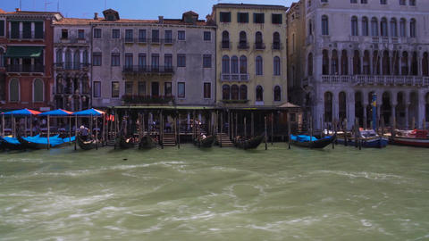 Parked gondolas and vaporettos, view of tour boats along Grand Canal in Venice Footage