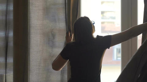 Woman opening dark curtains letting warm summer sun in her cozy home, slowmotion Footage