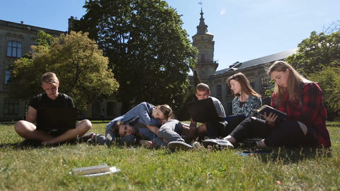 Group of tired students studying hard on park lawn Footage
