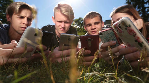 Friends in circle using smartphones on park lawn Footage