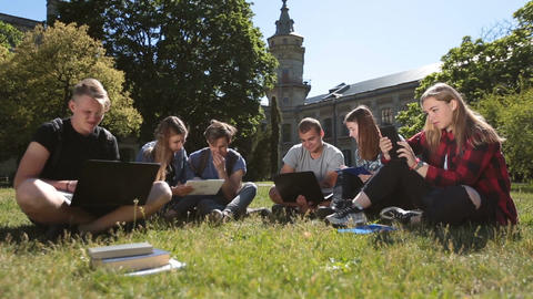 Students studying with laptop and tablet on grass Image