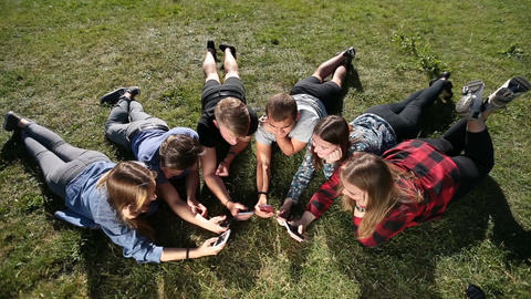 Top view teenagers in circle using phones in park Live Action