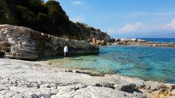 Woman on the beautiful natural rock beach of Kassiopi, Corfu Island, Greece, Ion