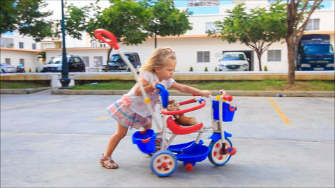 Little Blond Girl Pushes Pram Tricycle about Play Ground Footage