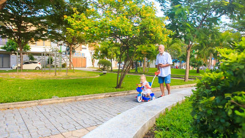 Grandpa Pushes Tricycle with Little Girl Reads Smartphone in Park Footage