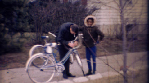 1971: African girl jokes caucasian man fixing bicycle Footage