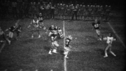 1978: High school football night game quarterback throws interception pass Footage