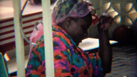 1969: African old women in colorful shirt and hair curler rollers Footage