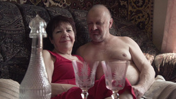elderly couple sitting on the couch, glasses of wine Footage