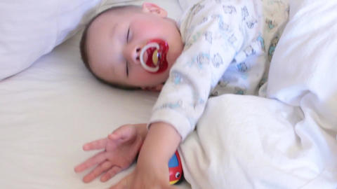 baby with a pacifier sleeping and waking Footage