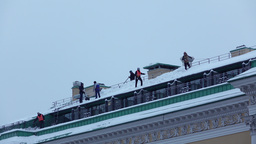 Group of cleaners remove snow from historical building roof, telephoto view Footage