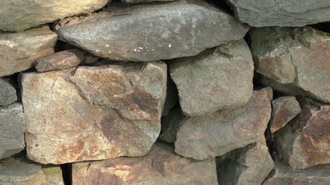 Wall of stacked slabs of stone. Dry wall built without mortar. Detail close up Footage