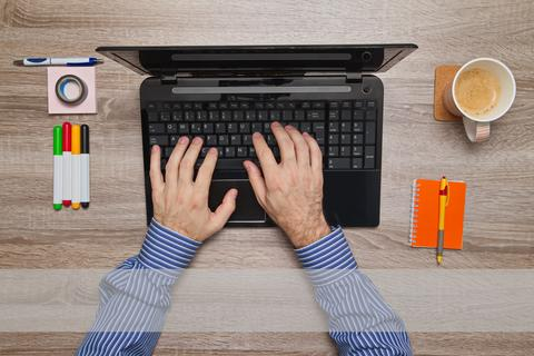 Male hand typing on laptop フォト