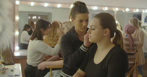 Makeup artist makes a girl beautiful makeup before photo shooting Live Action