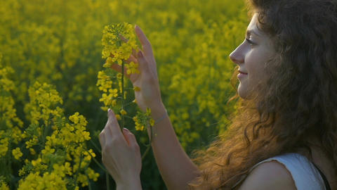 Dreaming girl holding a flower relaxing and enjoying the summer sunset standing  Footage
