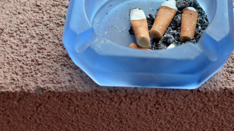 Cigarette butts with ash in glass ashtray Footage