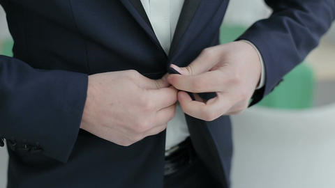 Buttoning a jacket. Stylish man in a suit fastening buttons on his jacket prepar