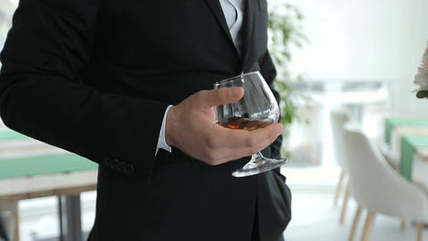 Groom holds in one hand a glass of whiskey
