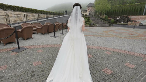 The bride in a beautiful long white dress walking to her husband