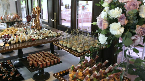 Beautifully decorated catering banquet table with different food snacks and appe Live Action