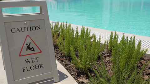 Caution wet floor sign on outdoor swimming pool Footage