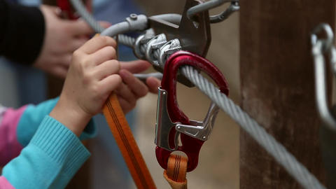 Girl clips a carabiner on the metal rope Footage