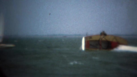 1979: Sailboat crash flipped over man climbs on top to wait for help Footage