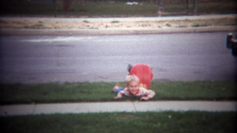 1979: Boy wipes out peddling a cart into grass near cars Footage