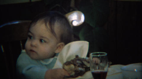 1971: Baby eating giant holiday turkey leg at dinner table Footage