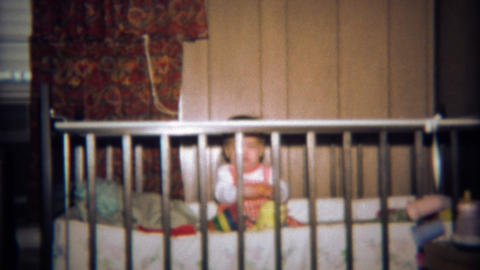 1971: Baby stuck behind crib bars and closeup toy in mouth Footage