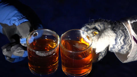 Two glass cup with hot tea touch in slow motion, winter night outdoor shot Footage