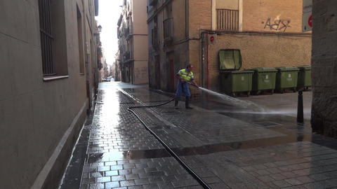 Man washes a street paved with stone cube with water using a hose. Two people, a Footage