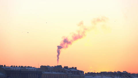 Biting frost winter sunset sky over old city buildings, smoke slow curl up Footage