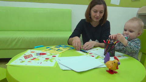 Mother And Little Baby Plays With Pencils stock footage